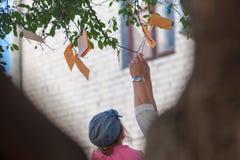 Hängninganmärkningar med önska på ett träd, anmärkningar av orange färg arkivbild
