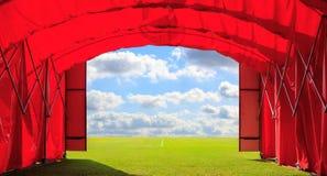 Hänrycka den röda porten av fotboll- eller fotboll- eller baseballstadion med molnbakgrund för blå himmel Begrepp av tillfället t Arkivbild