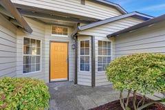 Hänrycka farstubron med den gula ytterdörren och stora fönster royaltyfri foto