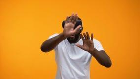 Häpen Afro--amerikan man i VR-hörlurar med mikrofon som undersöker moderna teknologier, framtid arkivfilmer