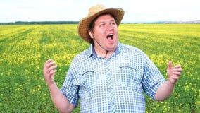 Häpen bonde, så chockat som extremt är lyckliga, med den breda öppna munnen i fältet på en solig dag med lyftta händer stock video