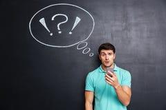 Häpen förbryllad ung man som använder mobiltelefonen över svart tavlabakgrund Royaltyfri Fotografi
