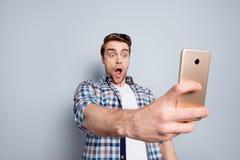 Häpen förskräckt grabb i rutiga skjortan som den har, genom att använda den smarta telefonen, Royaltyfri Bild