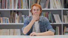 Häpen förvånad man med röda hår som undrar lager videofilmer