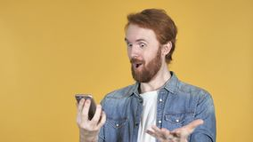 Häpen förvånad rödhårig manman, medan genom att använda Smartphone, gul bakgrund lager videofilmer