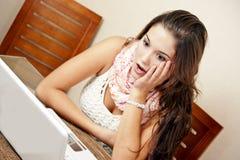 Häpen flicka framme av datoren Arkivfoto