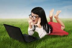 Häpen flicka med bärbara datorn på fält Royaltyfria Foton