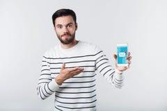 Häpen goda som ser den skäggiga mannen som pekar på mobiltelefonen fotografering för bildbyråer