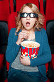 Häpen kvinna i exponeringsglas som äter popcorn Fotografering för Bildbyråer