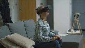 Häpen kvinna i VR-hörlurar med mikrofon arkivfilmer