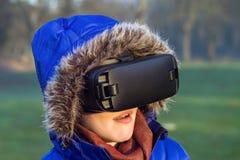 Häpen kvinna som bär VR-hörlurar med mikrofon i naturen royaltyfri foto