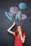 Häpen kvinna som står över svart tavlabakgrund med utdragna ballonger Royaltyfria Bilder