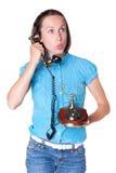 Häpen kvinna som talar i den retro telefonen Fotografering för Bildbyråer