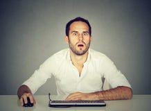 Häpen man som använder datoren på skrivbordet royaltyfri foto