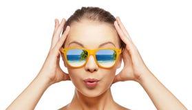 Häpen tonårs- flicka i solglasögon Arkivfoto