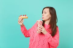 Häpen ung kvinna i den stack rosa tröjan som ser på eclairkakan och dricker cola eller sodavatten från den plast- koppen som isol arkivbilder
