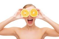Häpen ung kvinna med orange skivor Royaltyfri Foto