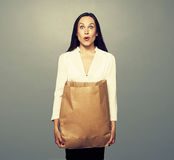 Häpen ung kvinna som rymmer den pappers- påsen Arkivfoton
