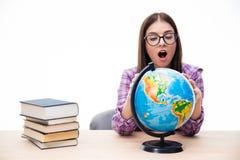 Häpen ung kvinnlig student som ser jordklotet Arkivbild
