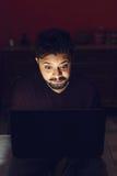 Häpen ung man som ser bärbar datordatoren i mörker Royaltyfria Foton