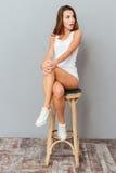 Häpet brunettkvinnasammanträde på stolen och se bort Arkivfoto