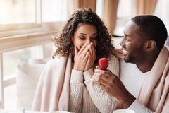 Häpna afrikansk amerikanpar som får förlovade i kafét Arkivbild