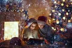 Häpna barn som använder minnestavlan nära julgranen Royaltyfri Foto