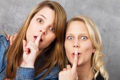 Häpna flickor som hyssjar - shh Arkivfoton