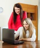 Häpna kvinnor som använder bärbara datorn Arkivfoton