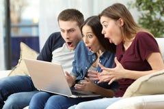 Häpna vänner som håller ögonen på innehållet på linje i en dator royaltyfri fotografi