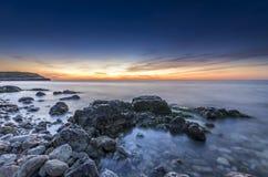 Häpnadsväckande stenig seacost efter solnedgång stock illustrationer
