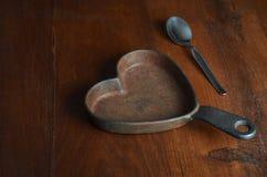 Härden formade gjutjärnkastrullen med silverteskeden på trä Royaltyfri Fotografi