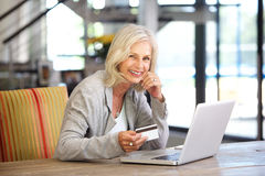 Härlig äldre kvinna med den bärbar datordatoren och kreditkorten arkivbild