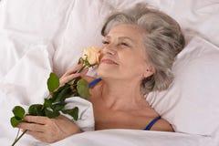 Härlig äldre kvinna som vilar i sovrummet Arkivfoton