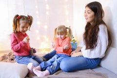 Härlig äldre syster som har roligt och spelar med små flickor Royaltyfria Bilder