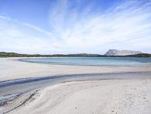 Härlig öde vit strand i Sardinia, Lu Impostu, med havet i olika skuggor av blått, kurvor av sand som markeras av vatten och royaltyfria bilder
