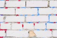 Härlig abstrakt bakgrund från den grungy smutsiga vita tegelstenväggen Med kvarlevor av målarfärg och fläckar från grafitti Urban royaltyfri foto
