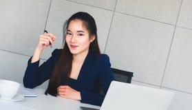 Härlig affärskvinna för asiatiskt långt hår i det marinblåa dräktleendet som så är lyckligt på hennes tabell i regeringsställning royaltyfri foto