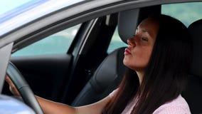 Härlig affärskvinna i bil som lyssnar till musik och dansar sammanträde i fåtölj lager videofilmer