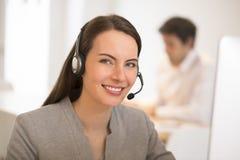 Härlig affärskvinna i kontoret på telefonen, hörlurar med mikrofon Arkivbilder
