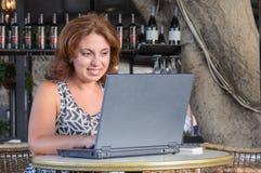 Härlig affärskvinna som arbetar med bärbara datorn i kafé Arkivbild
