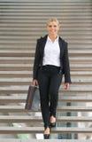 Härlig affärskvinna som går bottenvåning med portföljen Arkivbild