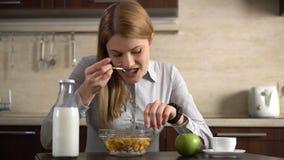 Härlig affärskvinna som har frukosten och använder hennes smarta klocka Bläddra internet Läs- nyheterna arkivfilmer