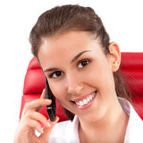 Härlig affärskvinna som i regeringsställning talar på mobiltelefonsammanträde på en röd stol Royaltyfri Foto