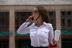 Härlig affärskvinna som stannar till telefonen royaltyfri foto