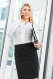 Härlig affärskvinna som talar på telefon- och innehavprofilen Arkivbild