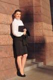 Härlig affärskvinnastående nära den rosa väggen med tegelplattan Royaltyfri Fotografi