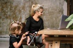 Härlig affärsmoder med hennes liten flicka arkivbild