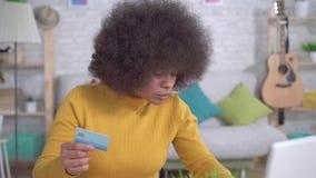 Härlig afrikansk amerikanflicka med en afro frisyr med en kontokort i hand och en bärbar dator i den moderna lägenheten lager videofilmer