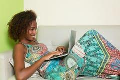 Härlig afrikansk amerikankvinna med anteckningsboken på soffan Arkivfoto